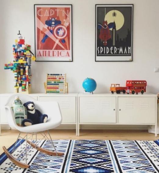 Ambiente com decoração de Super-Heróis, armário baixo branco, tapete étnico, cadeira de balanço e quadros  na parede.