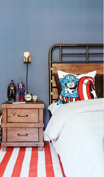 Quarto com decoração, Almofadas de super-heróis, bonecos, criado mudo de madeira, cama e tapete com listras vermelhas e brancas.