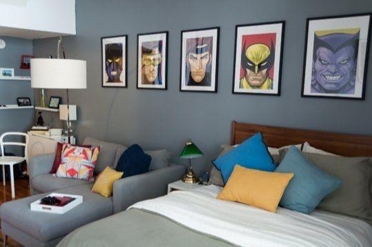 Quarto com decoração de Super-heróis. Sofá de canto cinza, cama, paredes com pintura de cinza e quadros de Super-heróis.