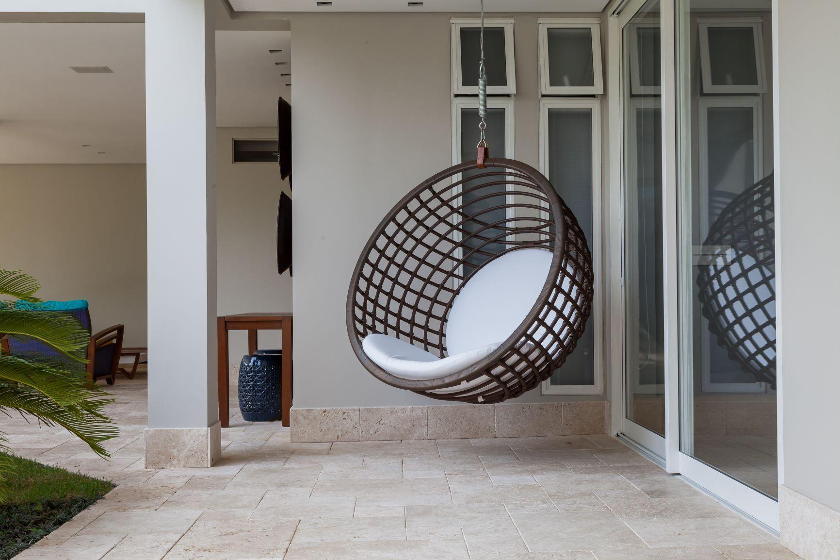 área externa com piso revestido de pedras naturais e cadeira balanço suspensa.