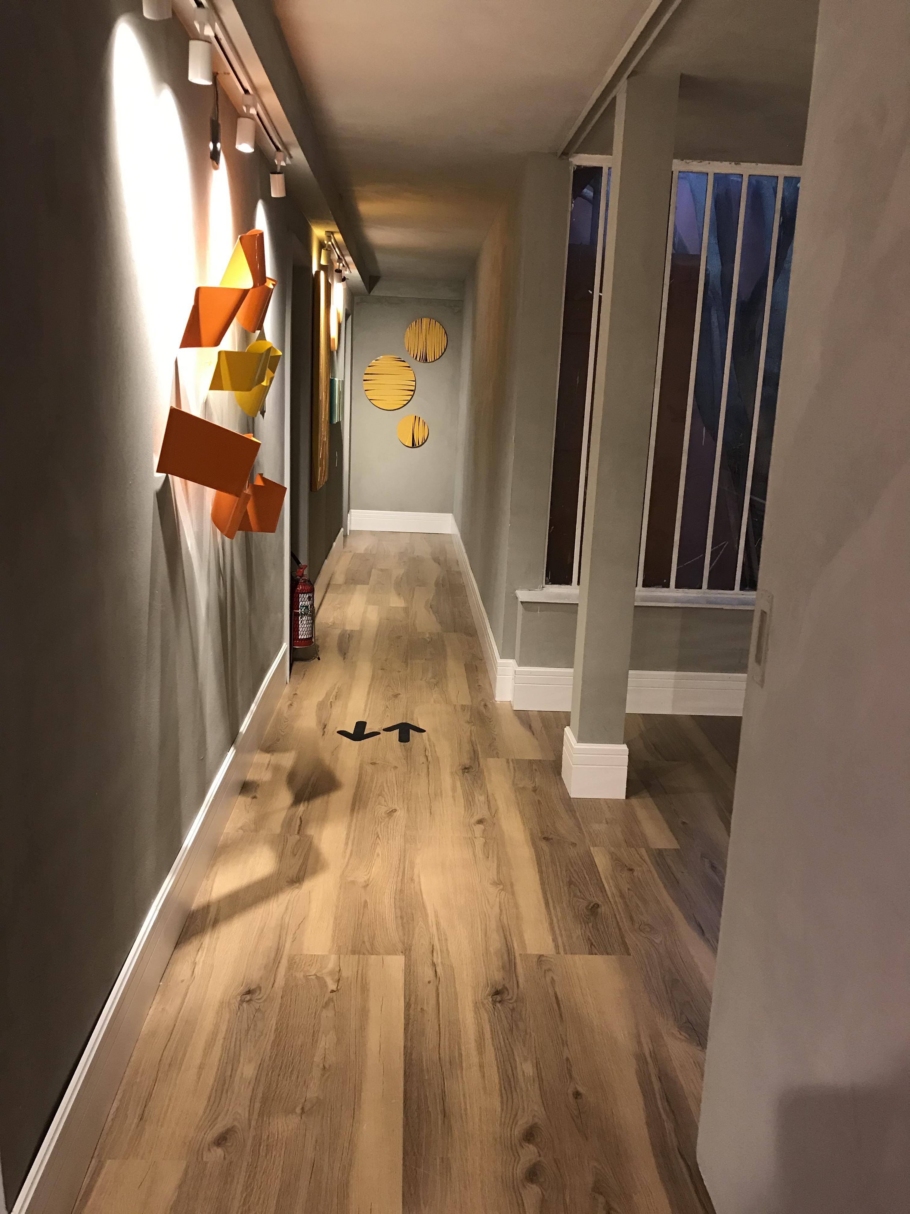 Corredor com piso laminado que imita madeira, rodapé branco e paredes com cimento queimado