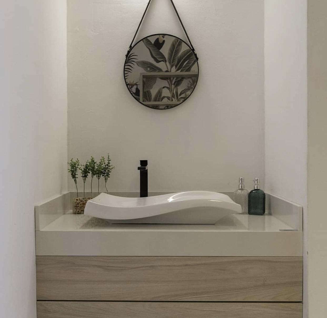Banheiro com espelho de alça redondo e cuba de apoio branca e gabinete de MDF