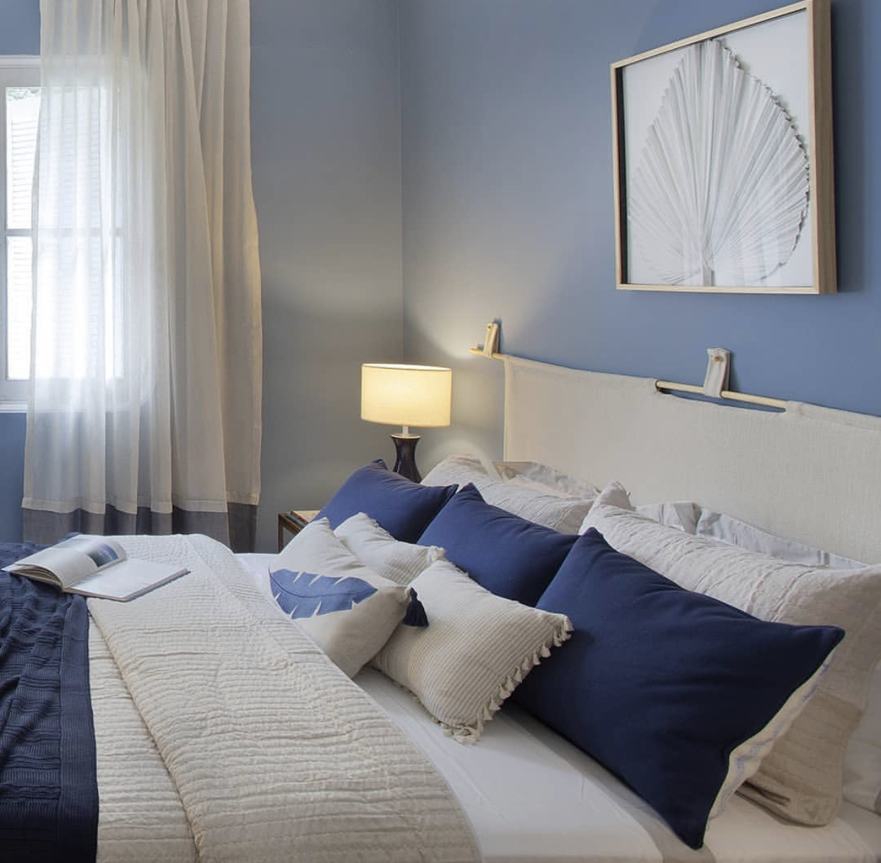 quarto com cama de casal com pintura e travesseiros azul e rodapé eucatex  Acqua Reveste