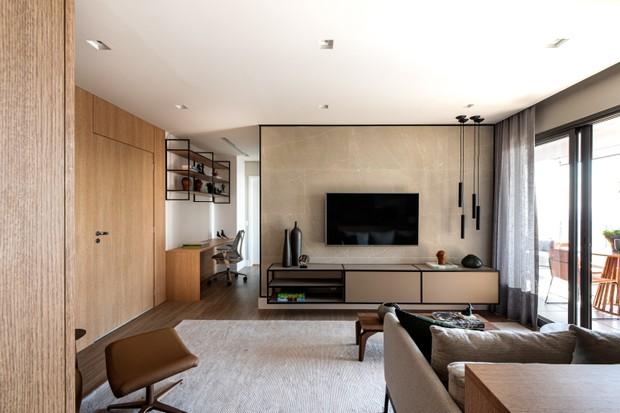 Sala pequena com cor neutra, paredes revestidas de madeira