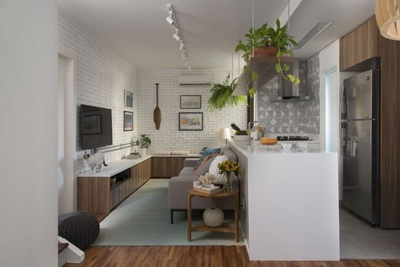 Sala pequena integrada com cozinha, com tijolinho branco,azulejo geométrico,plantas e sofá cinza