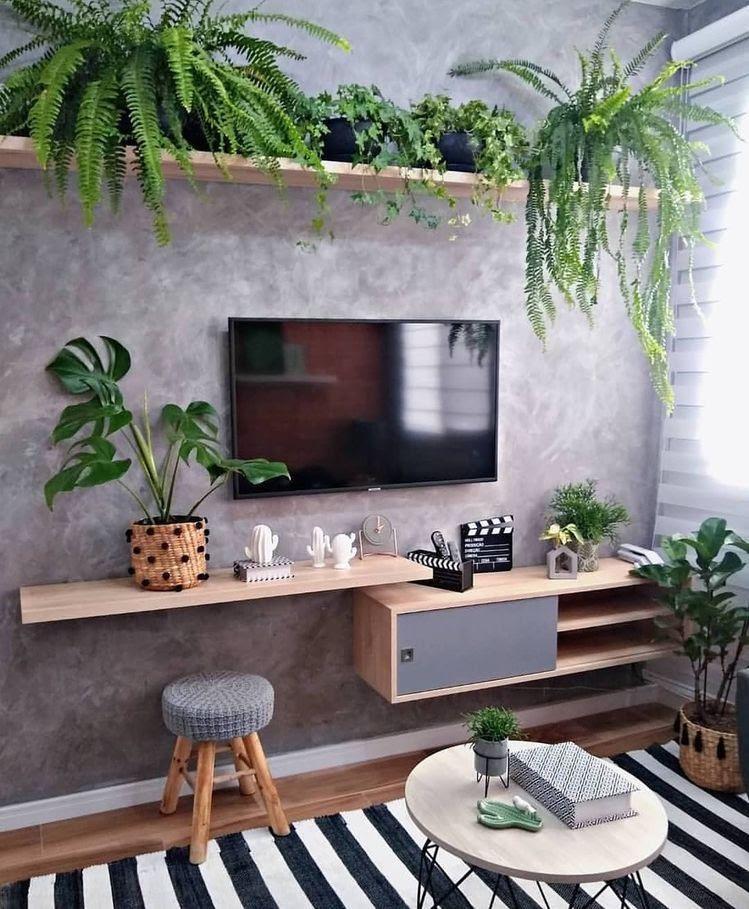 Sala de estar pequena com parede em cimento queimado e chão de madeira, estilo urban jungle