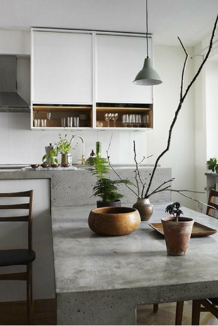 Cozinha com mesa, pia e bancada revestida com cimento queimado, luminária pendente e vasos de plantas compondo a decoração