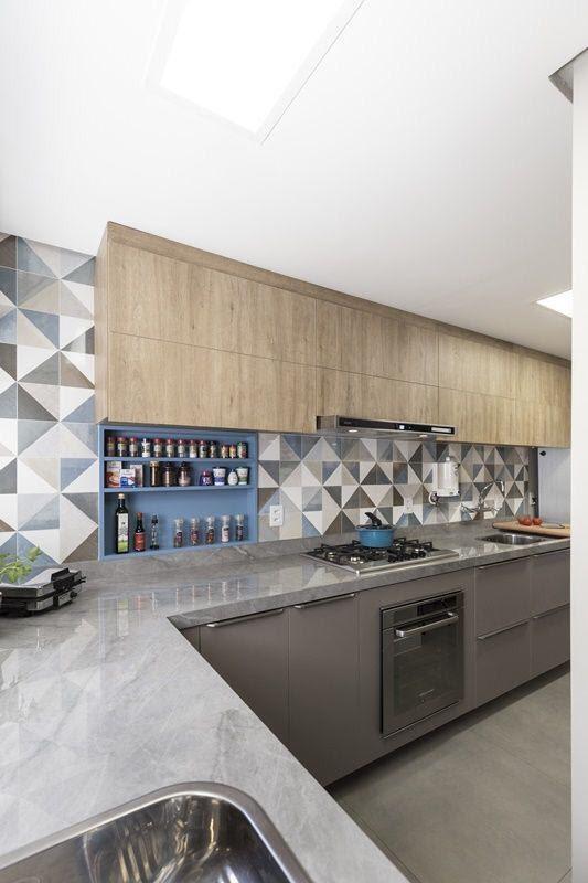 Cozinha moderna com bancada de porcelanato, armários de madeira e azulejo de ladrilhos azul, branco e cinza.