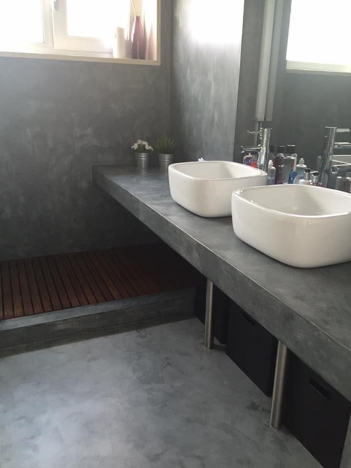 Banheiro todo revestido com cimento queimado e pequeno deck de madeira na lateral