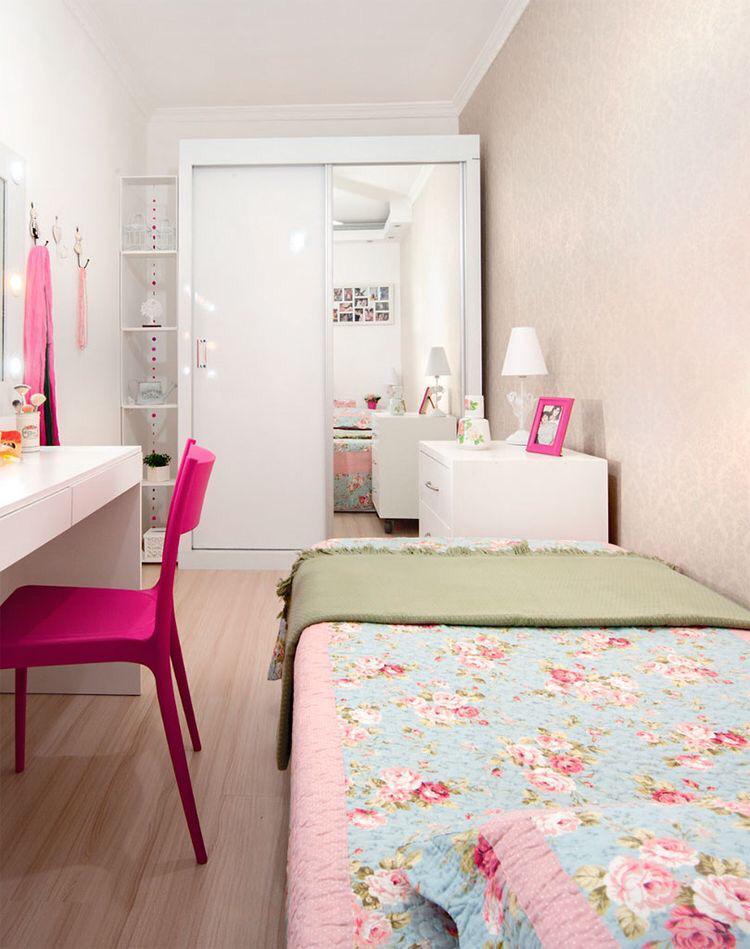 quarto menina pintado de rosa, com guarda roupa branco, cadeira rosa e roupa de cama florida