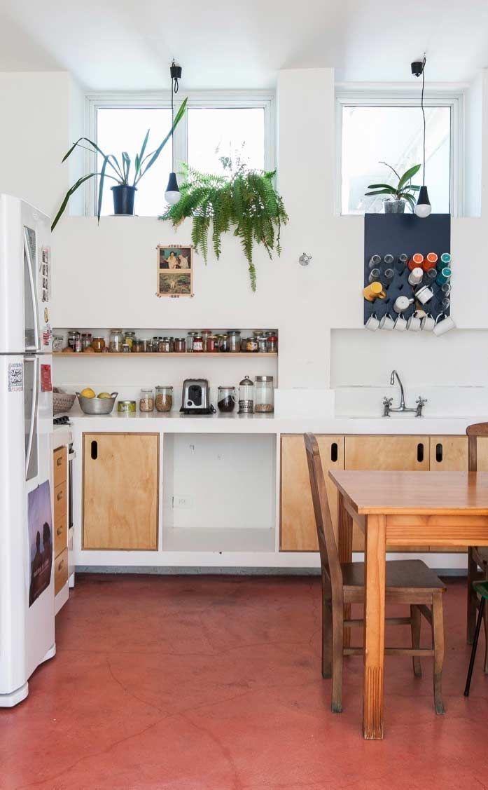 Cozinha com chão de cimento queimado vermelho, mesa, cadeiras,  portas e gavetas de madeira