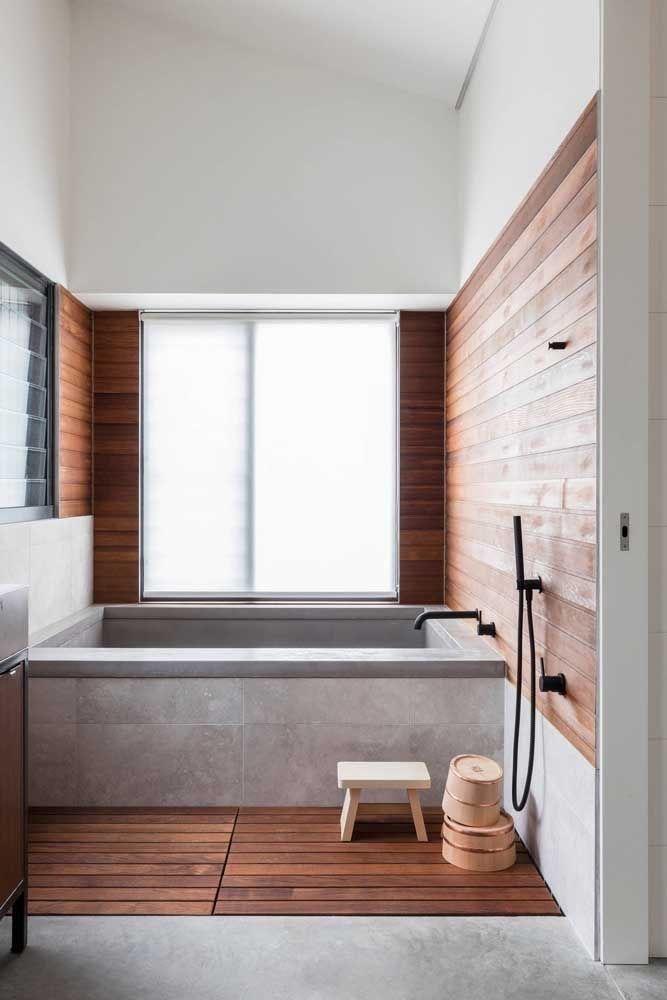 Banheiro com banheira revestida de cimento queimado, paredes de madeira e uma janela grande deixando o ambiente iluminado