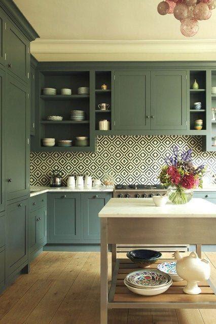 Cozinha com armários verdes, piso amadeirado, mesa de madeira e azulejo de ladrilhos.