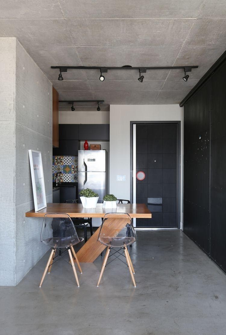 Apartamento estilo industrial, todo revestido de cimento queimado, mesa de madeira e porta na cor preta