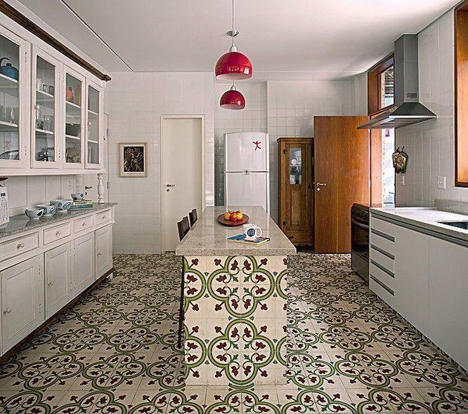 Cozinha grande com azulejos brancos, bancada de mármore, luminárias pendente e armários brancos e piso de ladrilhos.