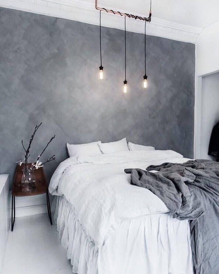 Quarto de casal com parede da cabeceira da cama revestida de cimento queimado e iluminaria pendente