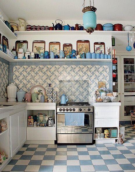 Cozinha clássica com decoração em tons de azul, fogão cinza, armário branco, azulejo de ladrilhos azul e branco, prateleiras brancas com utensílios azuis, vermelhos e branco