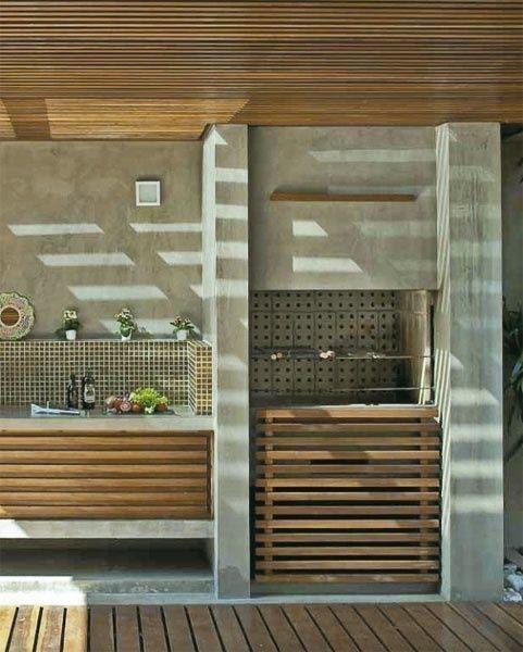 Área externa com churrasqueira e bancada revestida de cimento queimado com detalhes em madeira