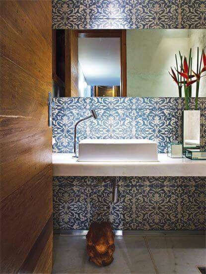 Lavabo com porta de madeira, piso porcelanato, cuba branca, espelho retangular e azulejo de ladrilhos azuis e brancos.
