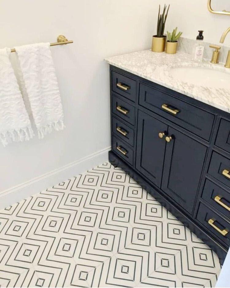 Banheiro com armário azul com detalhes dourado, acessórios dourado no banheiro, parede pintada de branca e piso de ladrilhos.