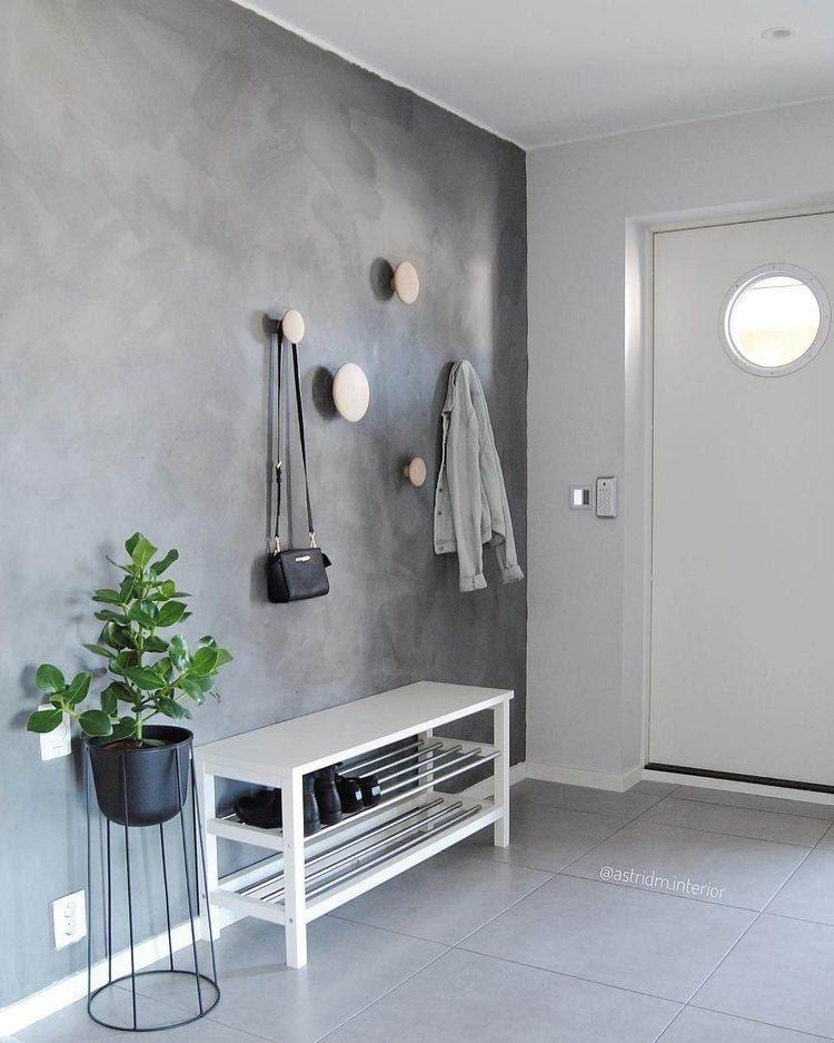 Hall de entrada de apartamento com parede revestida de cimento queimado com vaso de planta para compor o ambiente