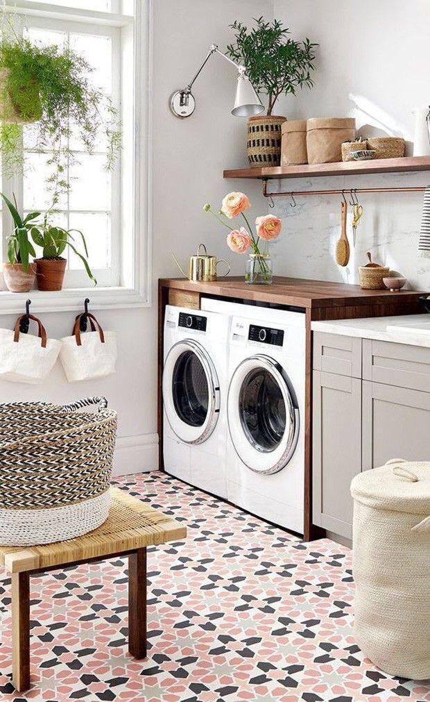Lavanderia com prateleiras de madeira, cestos de palha, parede pintadas de branco, plantas e piso de ladrilhos rosa, preto e branco.