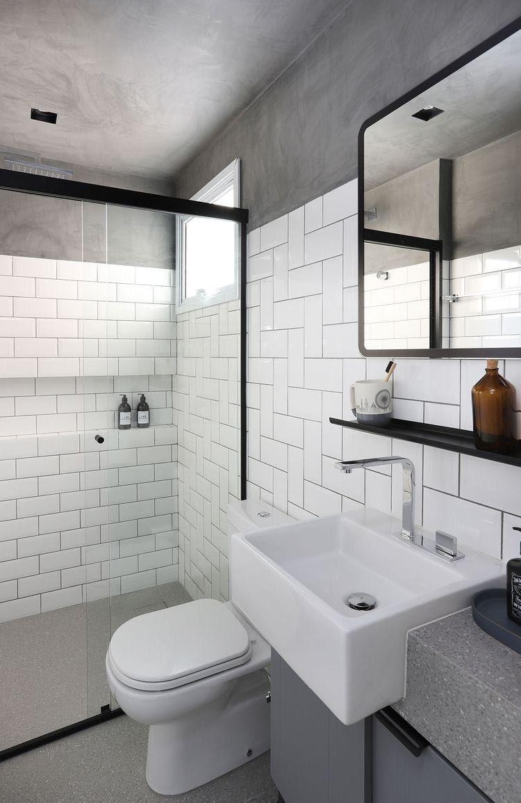 Banheiro revestido com azulejos brancos e detalhes de cimento queimado, deixando-o mais sofisticado