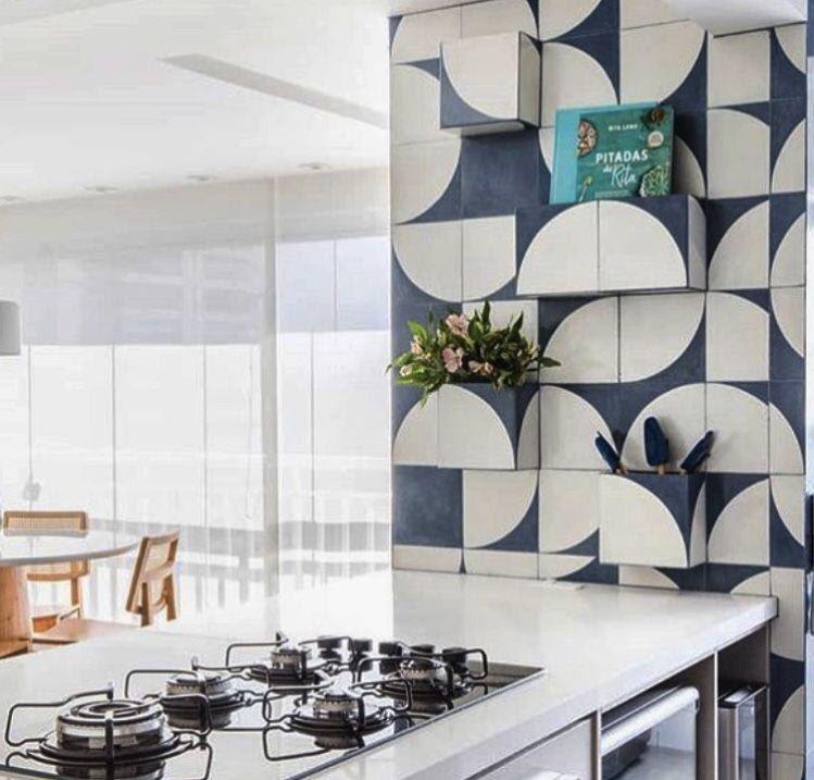 Cozinha com azulejo de ladrilhos azul e branco e bancada de porcelanato branco com cooktop.