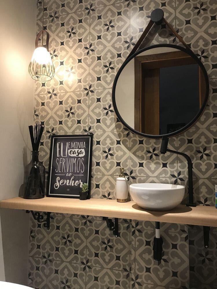 Banheiro em tons escuros com azulejo de ladrilhos, espelho redondo, pia branca, banca de madeira e acessórios decorativos.