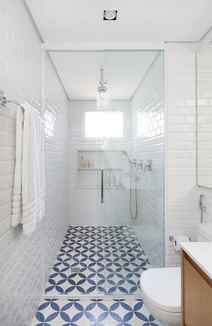 Banheiro com paredes revestidas de azulejo do metrô branco, piso de ladrilhos azul e branco e box de vidro.