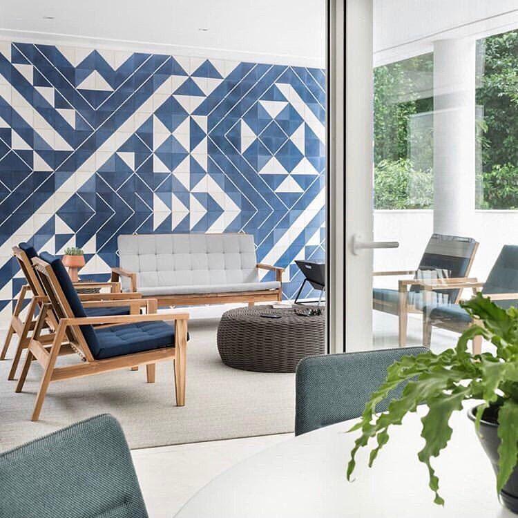 Ambiente com poltronas de madeira com estofado azul e sofá com estofado cinza, tapete cinza, mesinha de centro de palha e parede com azulejo de ladrilhos azul e branco
