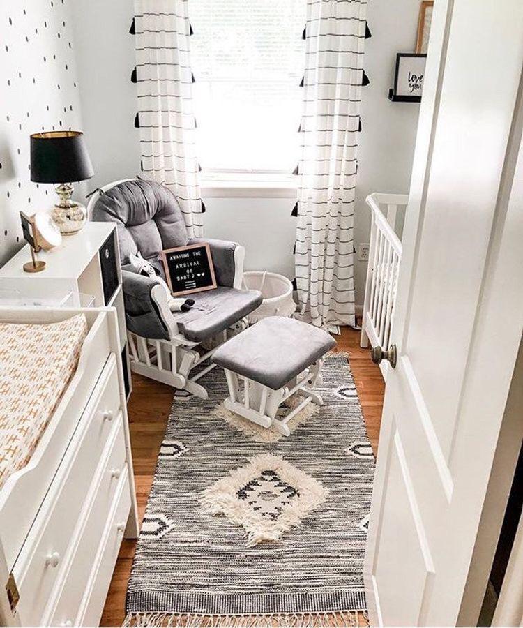 Quarto de bebê pequeno com cadeira de amamentação branca de estofado cinza, berço, demais móveis brancos, tapete cinza e abajur preto.