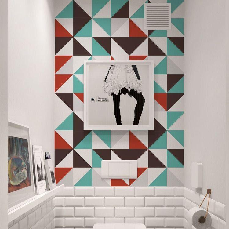 Banheiro com papel de parede que simula ladrilhos coloridos, meia parede com azulejos do metrô branco, quadro na parede e quadros posicionados.