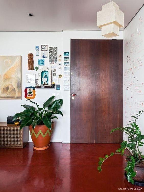 Apartamento com paredes revestidas em cimento queimado, piso de madeira e ambiente com vasos de plantas na decoração