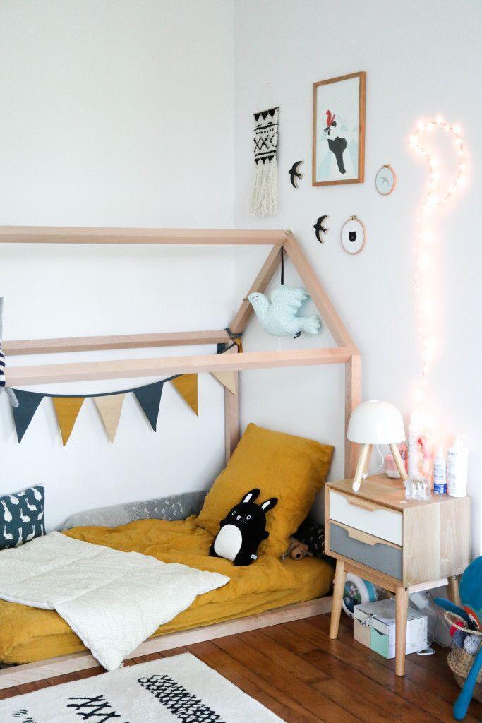 Quarto de criança com cama montessoriana, piso de madeira e criado mudo com gavetas coloridos.