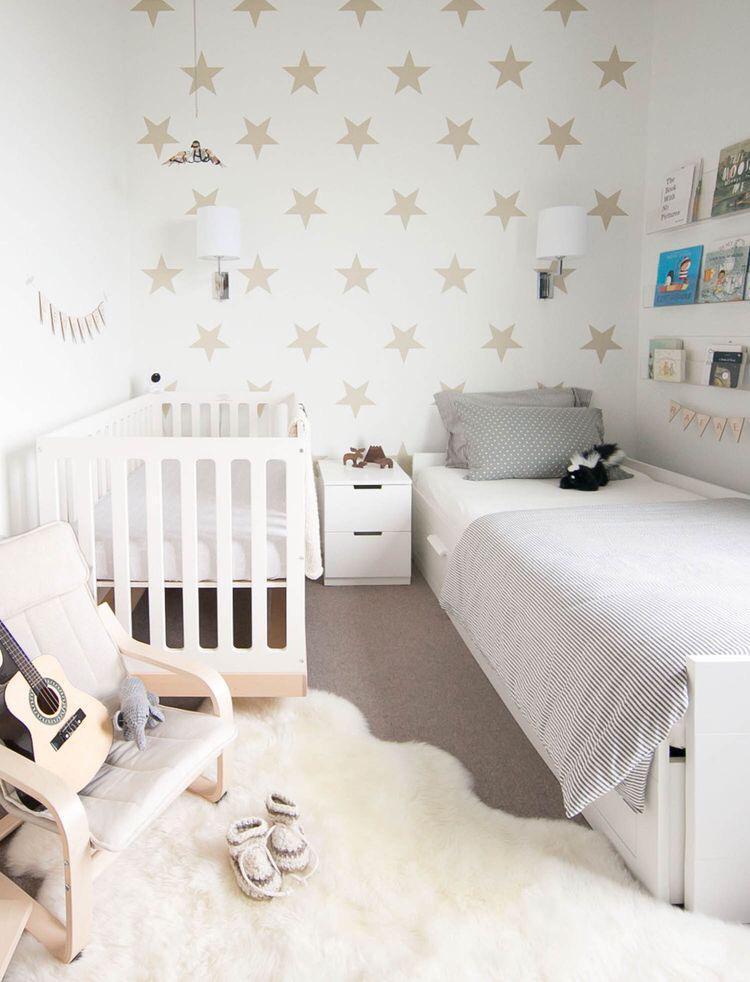 Quarto de criança com berço e cama com cores neutras, parede branca com adesivos de estrelas e carpete no chão.