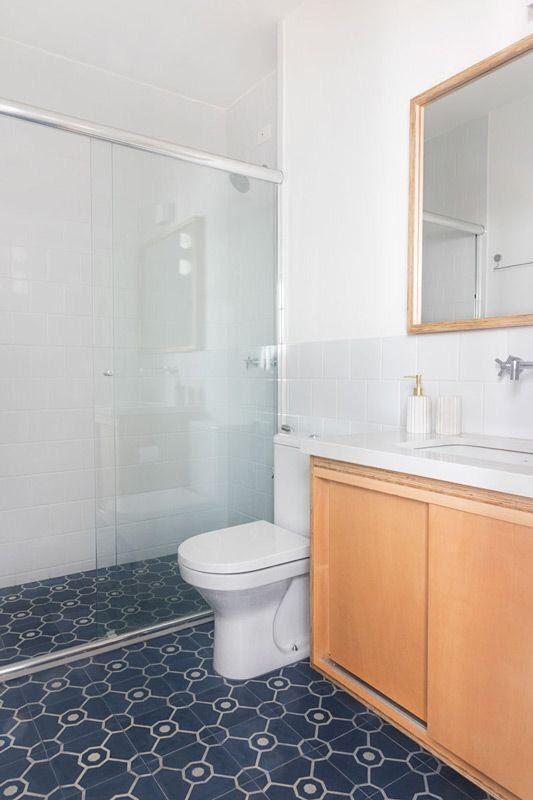 Banheiro com azulejo branco, armário de madeira, box de vidro e piso de ladrilho azul escuro com detalhes brancos.