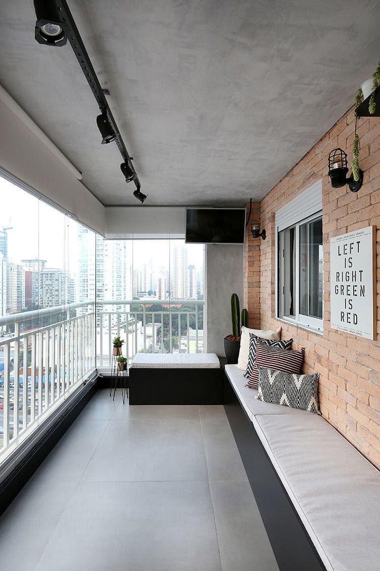 Varanda ampla de apartamento com paredes em cimento queimado e tijolinhos, vasos de plantas na decoração