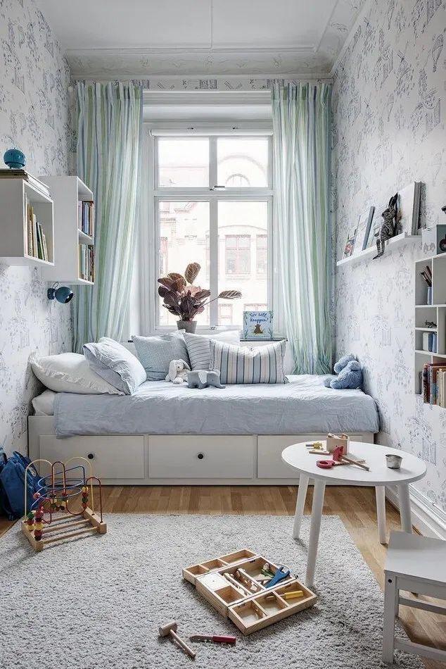 quarto com papel de parede floral feminino, piso de madeira, cama branca, cortina verde e mesinha de canto redonda branca.