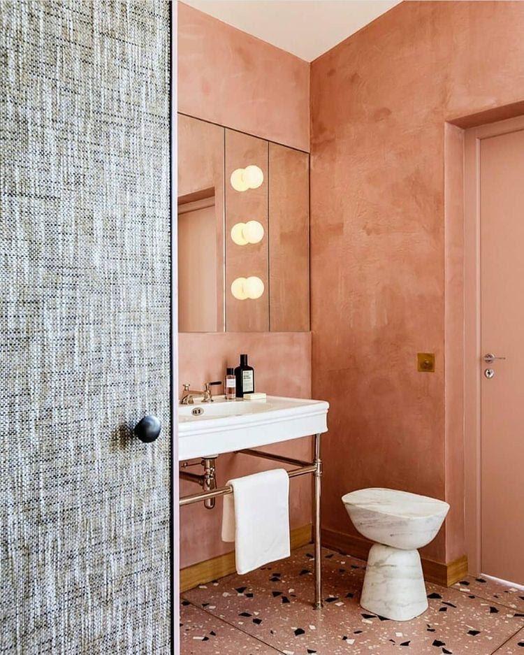 Lavabo revestido de cimento queimado na cor rosa, com luminárias fixas no espelho, piso de granilite