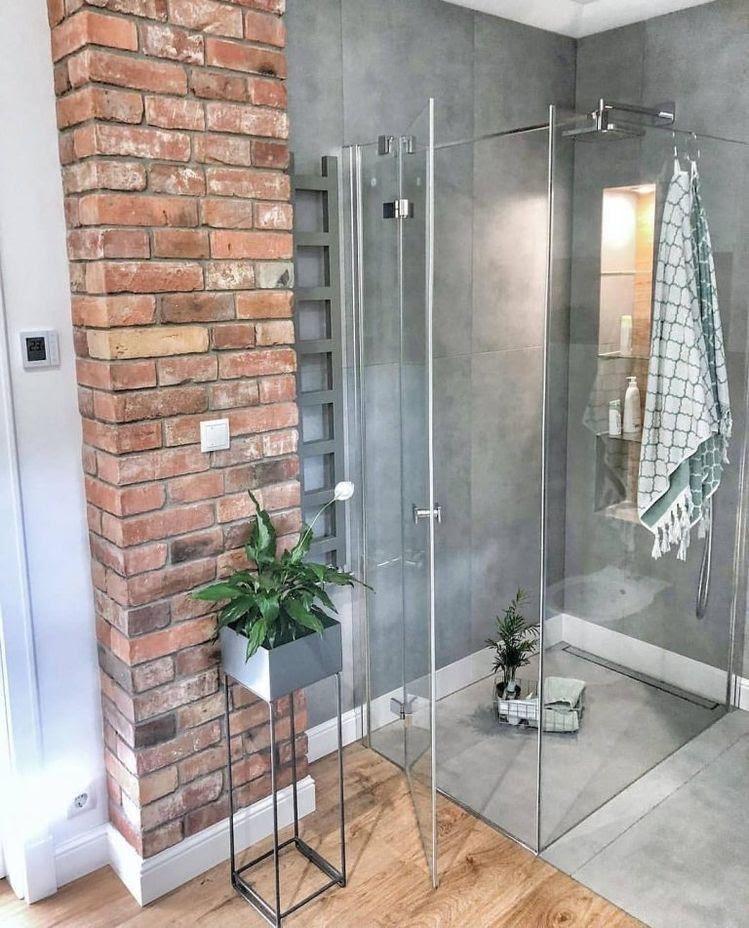 Banheiro com parede revestida de cimento queimado, com box de vidro e vasos de plantas para compor a decoração