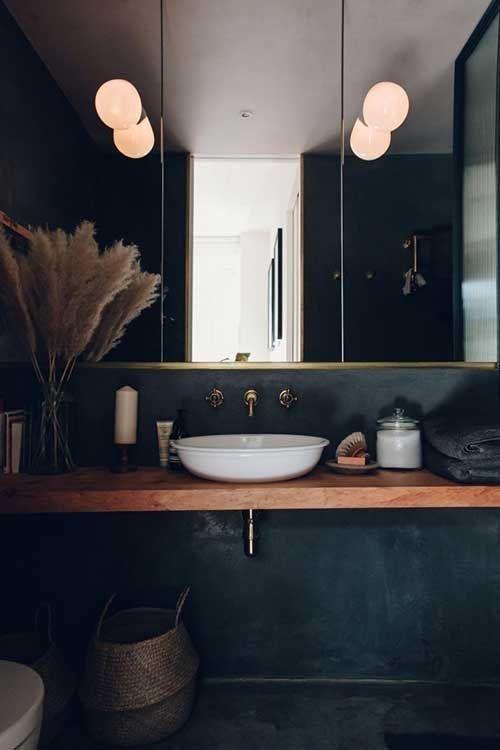 Banheiro revestido de cimento queimado preto com decoração em cores mais escuras e cuba de apoio