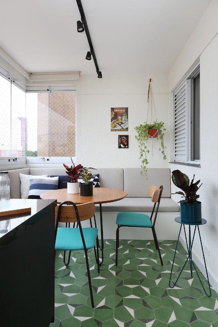 Varanda com sofá cinza, paredes pintadas de branco, ladrilhos verde com detalhes branco e preto, mesa redonda de madeira e cadeira com estofado verde.