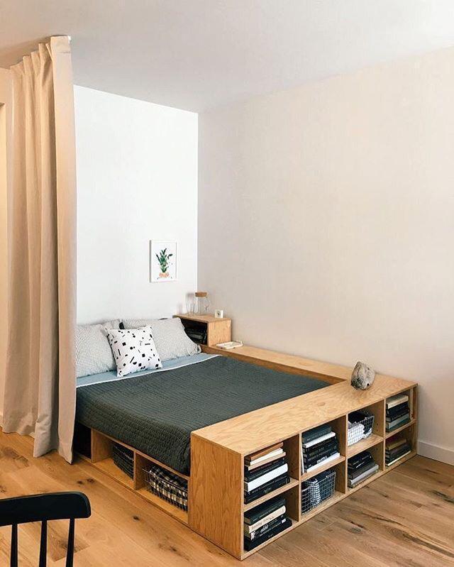decoração para quartos pequenos com movel embutido para colocar livros e se torna uma bancada, piso de madeira e paredes brancas.