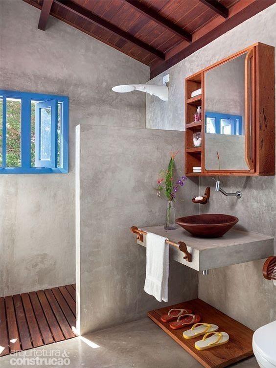 Banheiro rústico, todo revestido em cimento queimado e deck de madeira na parte do box