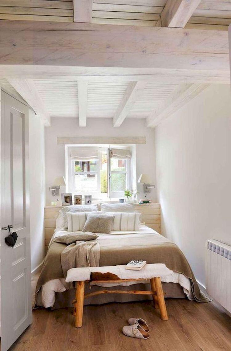 Quarto com teto de madeira branca, cama de casal, paredes e portas brancas, banquinho de madeira e piso de madeira.