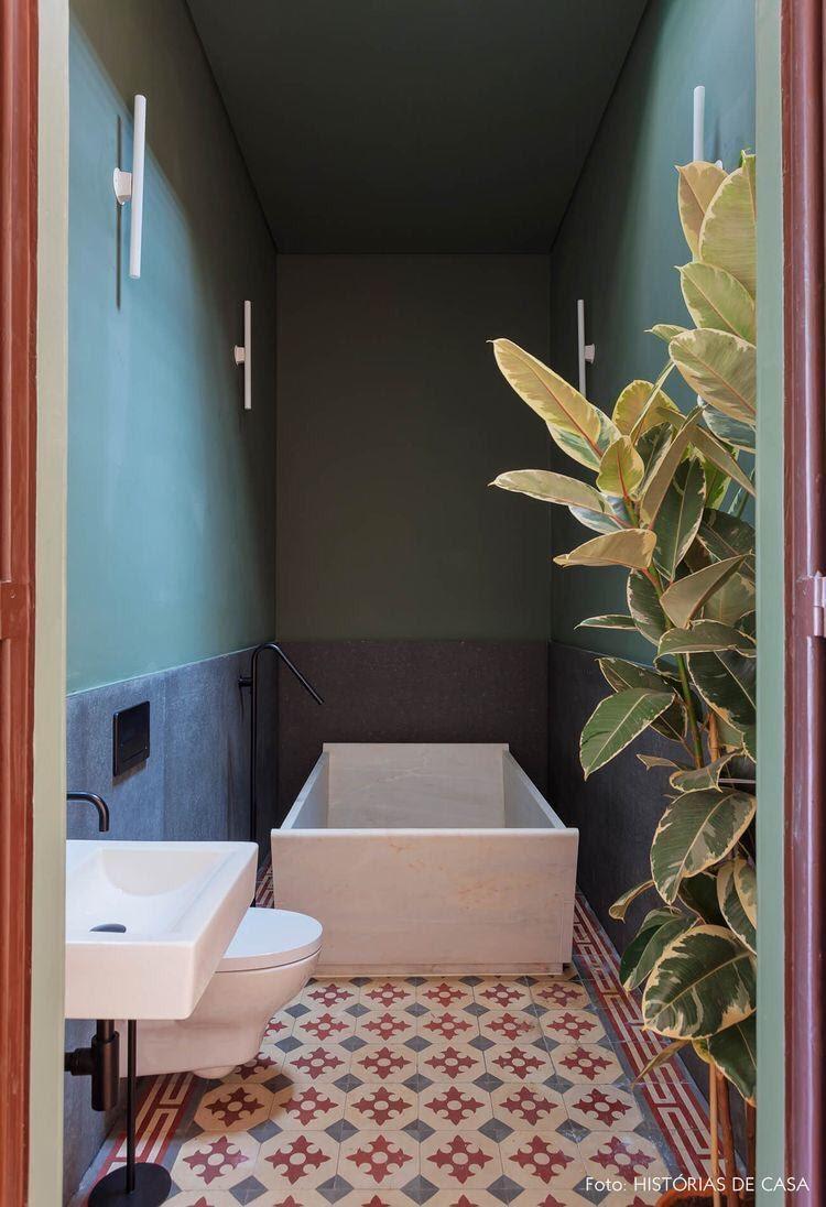 banheiro com louças brancas, banheira branca, paredes verde e azul, plantas e ladrilhos vermelho, azul e branco.
