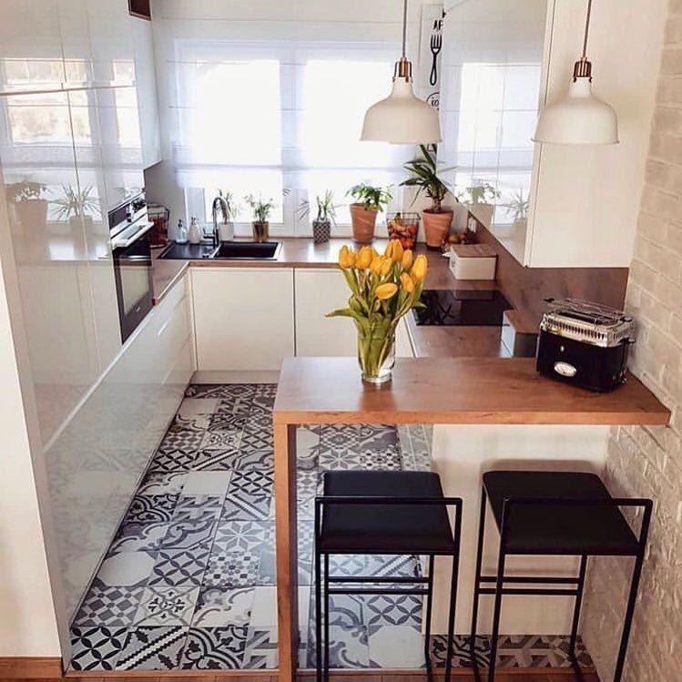 Cozinha com armário branco, luminárias pendente brancas, bancada de madeira com bancos pretos e piso de ladrilhos azuis.