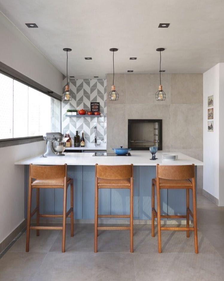 Cozinha revestida de cimento queimado, com luminárias pendentes e bancos de madeiras