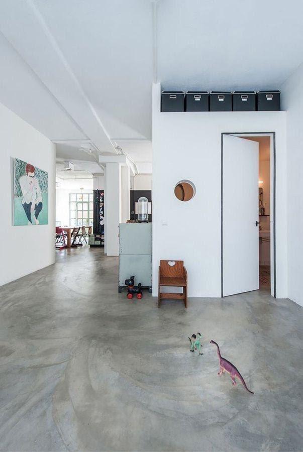 Ambiente com chão revestido de cimento queimado, com decoração minimalista na cor branca